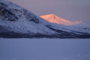 Den uppgående solen färga fjälltoppen i nordväst